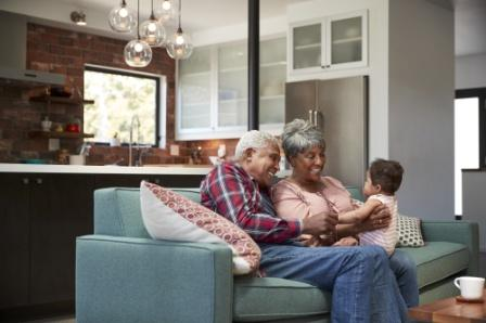 An older couple sit on their couch and smile as they hold their grandchild. They can provide for their grandchild and other family members by educating themselves on life insurance myths.