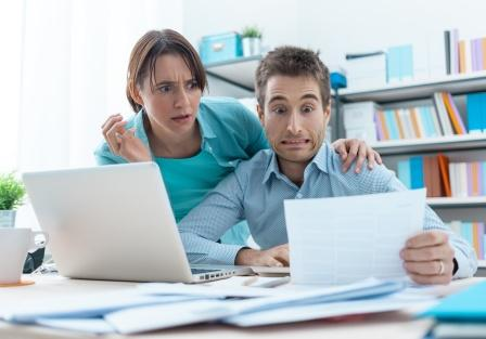 A couple looks in shock at a bill since they have fallen victim to surprise medical billing.